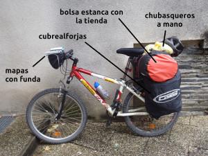 Bicicleta preparada para la lluvia con mapa enfundado en la cesta, cubrealforjas y tienda en la bolsa estanca