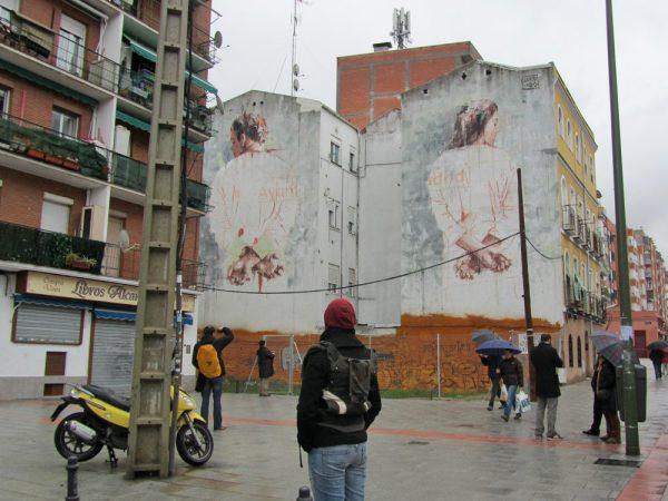 Graffiti sobre medianera que representa dos personas que parecen mani atadas. Sobre ellas se leen las palabras Ayuntamiento de Madrid