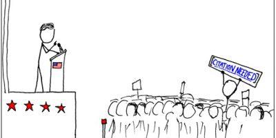 """Político o política habla en un podio. Entre la masa, alguien alza un cartel que reza: """"Cita requerida""""."""