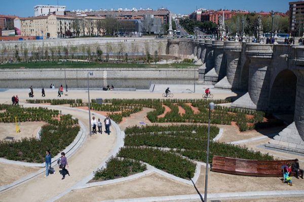 Gente pasea o recorre en bici el parque junto al río
