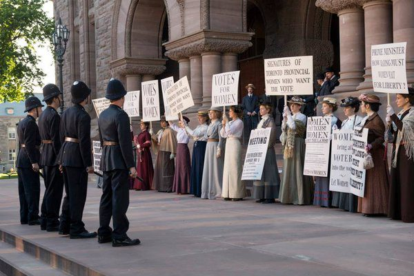 Manifestación de sufragistas con carteles ante la policía