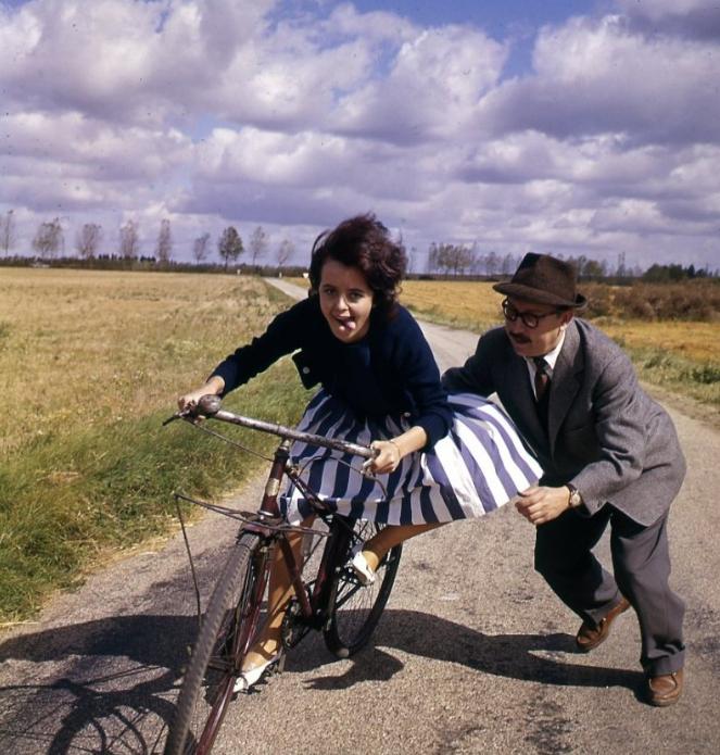 chica en una bicicleta sacando la lengua seguida por un hombre preocupado por que no se caiga