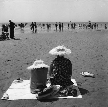 Una mujer en la playa con un sombrero peludo junto a una bolsa que lleva el mismo sombrero. Por el sombrero, ambos parecen personajes.