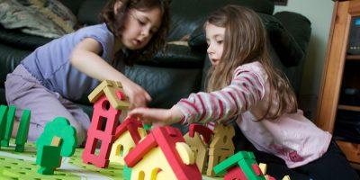 Dos niñas jugando con casas en el suelo y construyendo una pequeña ciudad.