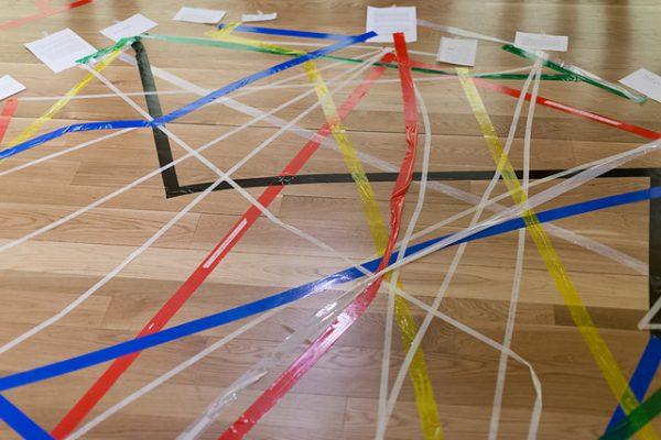 Cintas de colores creando una red que une distintos documentos sobre lo que parece una pista de un gimnasio. La imagen da la idea de red.