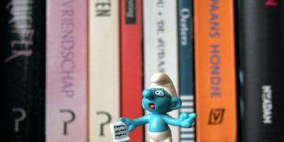 Muñeco de un pitufo con un papel frente a una pila de libros.