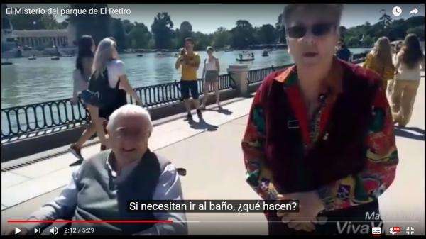 """Captura de un vídeo. Se ve a un señor mayor en silla de ruedas y una mujer. Están junto al parque del retiro. En los subtítulos se lee """"Si necesitan ir al baño, ¿qué hacen?""""."""
