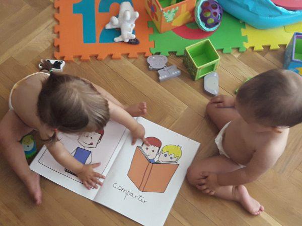 Dos bebés juegan con el libro ¿Para qué sirven los libros?