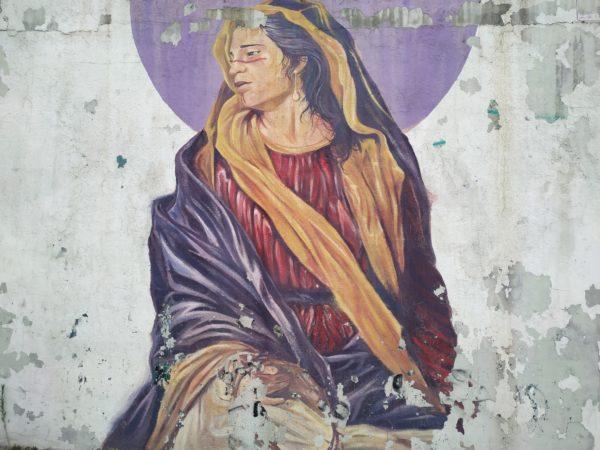 Mujer con vestimentas de virgen y maquillaje línea roja entre ojos y cruza nariz