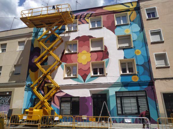 Mural que cubre todo un edificio con motivos florales y de mucho colorido