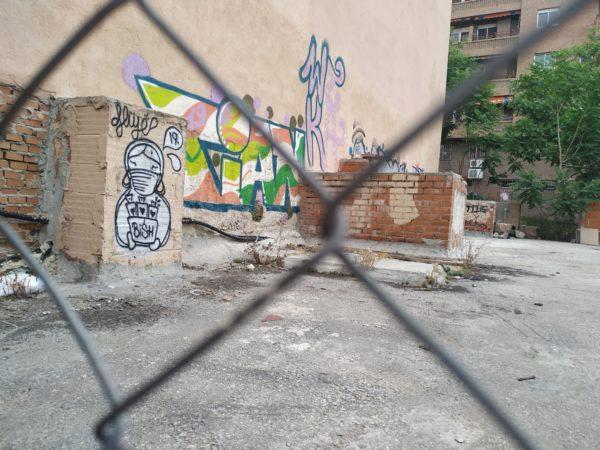 Tras verja, varios graffitis. En uno, un personaje lleva una mascarilla