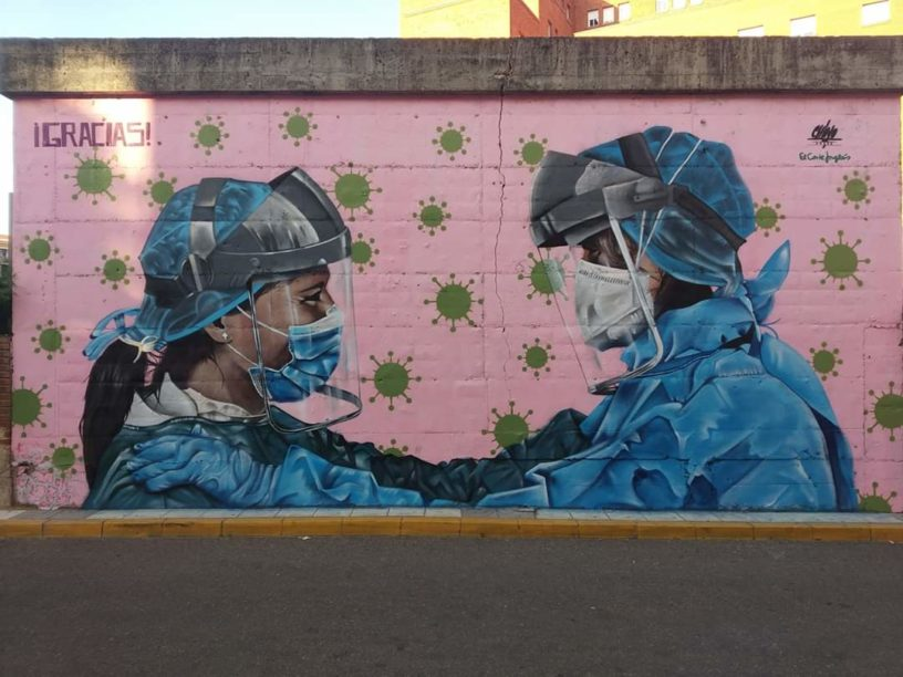 dos personas sanitarias con equipos de protección se miran... alrededor virus y la palabra gracias