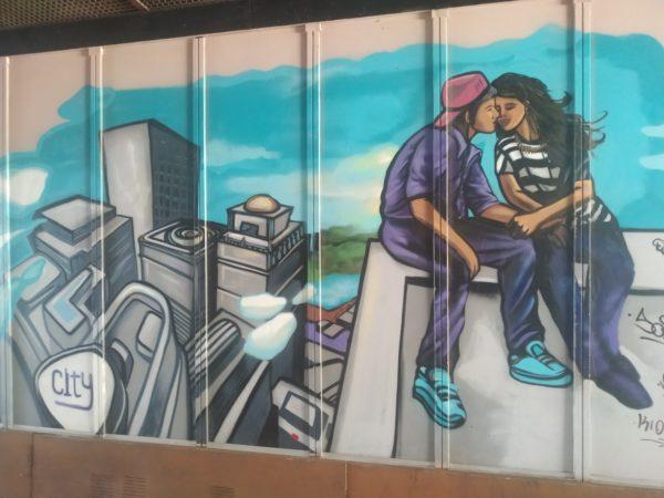 pareja acaramelada sobre edificio y edificios más bajos al fondo