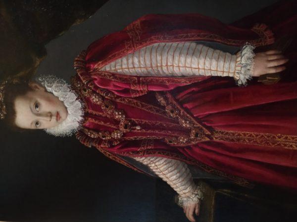 Joven en retrato típico de la realeza con camisa blanca, joyas, vestido rojo, muy colorido.